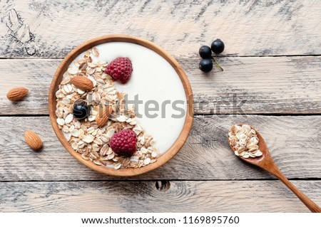 Healthy breakfast on wooden table. Bowl of muesli with natural yogurt, almonds and fresh raspberries. Top view.