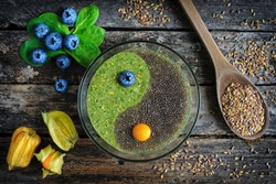 Healthy breakfast. Raw flaxseed porridge with chia seeds, spinach, physalis and fresh blueberries on wooden table, top view. Clean eating, dieting, vegetarian food concept