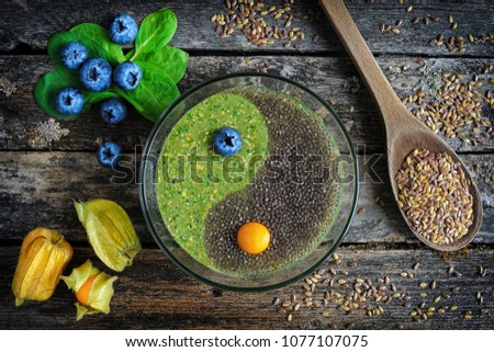 Photo of  Healthy breakfast. Raw flaxseed porridge with chia seeds, spinach, physalis and fresh blueberries on wooden table, top view. Clean eating, dieting, vegetarian food concept