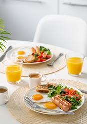 healthy breakfast served on white table (fried eggs, sausages, fresh vegetables and greens, coffee and orange juice), selective focus
