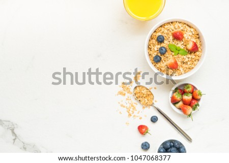 Healthy Breakfast set Granola with blueberry and strawberry and black coffee , Milk and Orange juice on white stone table background #1047068377