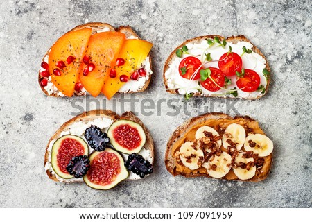 Healthy breakfast toasts with peanut butter, banana, chocolate granola, cream cheese, figs, blackberry, persimmon, pomegranate, chia seeds, tomato, micro greens. Top view, overhead