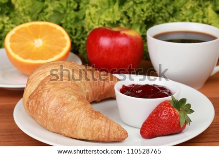 Healthy breakfast with a croissant and strawberry jam. Served with coffee and fresh fruits.