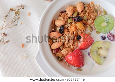 Healthy breakfast with fresh cereal milk, strawberry, kiwi, almond on the white bowl. dried flower,  and white cloth is background. minimal japanese style