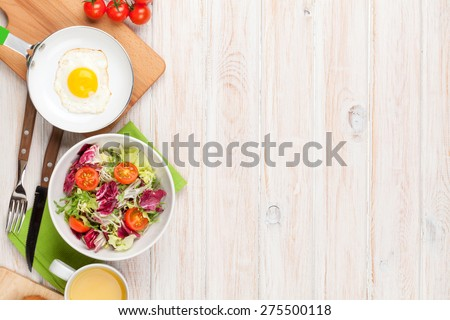 Healthy breakfast with fried egg, toasts and salad on white wooden table. Top view with copy space