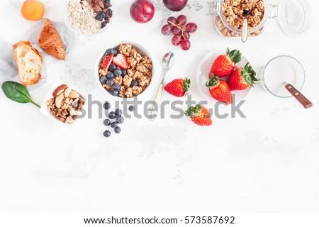 Healthy breakfast with muesli, fruits, berries, nuts on white background. Flat lay, top view. #573587692