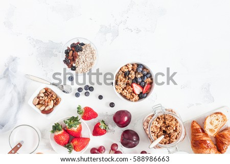 Healthy breakfast with muesli, fruits, berries, nuts on white background. Flat lay, top view