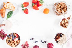 Healthy breakfast with muesli, fruits, berries, nuts on white background. Flat lay, top view, copy space.