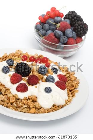 Healthy Breakfast with muesli, yogurt, raspberries, blackberries and blueberries on white background - stock photo