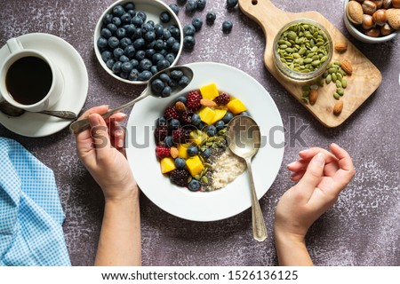 Healthy breakfast with oatmeal porridge, fruits and nuts. Blueberry, mango, pumpkin seeds, nuts, coffee cup. Top view. Female hands.