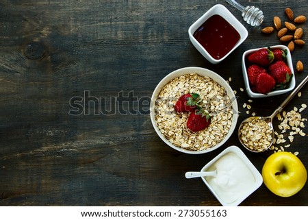 Healthy Breakfast. Yogurt with muesli and berries on rustic wooden background. Health and diet concept. Top view.