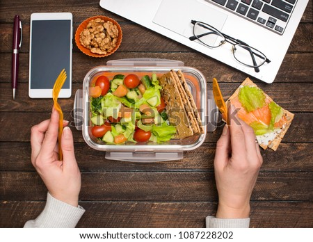 Healthy business lunch at workplace. Salad, salmon, avocado and bread crisps lunch box on working desk with laptop, smartphone, glasses.
