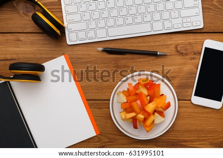 Healthy business lunch at workplace. Top view flat lay of desktop - laptop, notepad and phone on wooden desk background with plate of fruit salad snack, nobody, objects #631995101