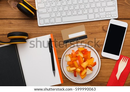 Healthy business lunch at workplace. Top view flat lay of desktop - laptop, notepad, credit card and phone on wooden desk background with plate of fruit salad snack, nobody, objects #599990063