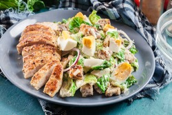 Healthy caesar salad with chicken, eggs, cheese and croutons. Italian cuisine