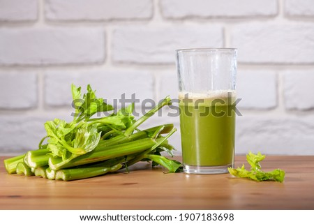 Healthy Celery diet for the treatment of incurable mysterious diseases. Fresh celery juice squeezed out on a juicer.drink, vegetable juice, studio shot Stockfoto ©