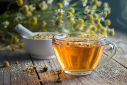Healthy chamomile tea or infusion, mortar and daisy herbs on wooden table.