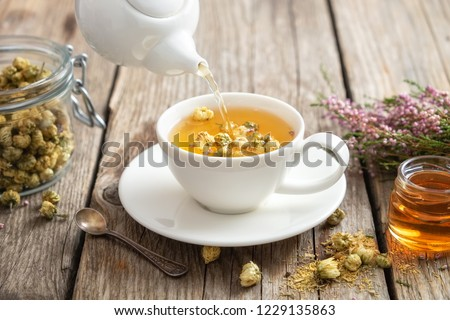 Healthy chamomile tea poured into white cup. Teapot, small honey jar,  heather bunch and glass jar of daisy medicinal herbs.