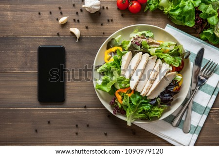 Healthy chicken salad next to smartphone on wood table background - mobile food ordering concept