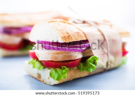 Healthy chicken sandwiches with lettuce salad, tomato and onion on blue wooden background close up.