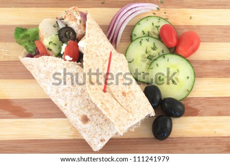 Healthy chicken wrap greek style with fresh vegetables, black olives, feta cheese and herbs