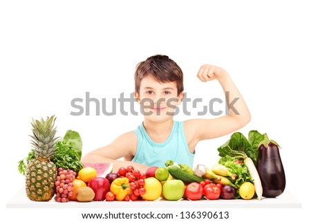 Healthy child showing his arm muscles and sitting on a table full of pile of fruits and vegetables