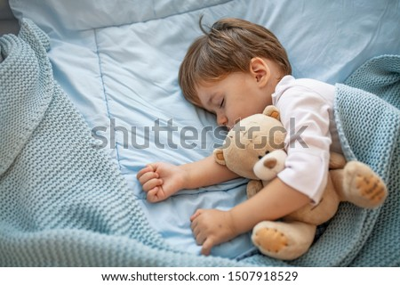 Healthy child, sweetest blonde toddler boy sleeping in bed holding her teddy bear. Adorable toddler girl taking a nap in a grey bed holding her teddy bear. Baby toddler asleep with teddy bear