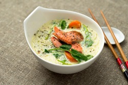 Healthy coconut thai soup closeup. One of the most popular Thai food, tom kha is a spicy and sour soup with coconut milk. Vermicelli noodles and salmon are added in this version of the dish.