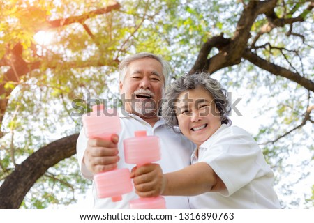 Healthy concept. Old couple have good health and look strong because elderly man and elderly woman love exercise at park in the morning. Grandfather and grandmother holding dumbbell with smiley faces