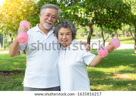 Healthy concept. Old couple have good health and look strong because elderly man and elderly woman love exercise or workout everyday. Grandfather and grandmother holding dumbbell with smiley faces