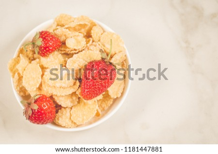 healthy concept with strawberry and flakes/strawberry and flakes in white bowls on a marble background. Top view and copy space #1181447881