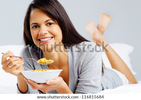 healthy cornflakes breakfast in bed woman eating and happy