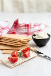 Healthy crisp rye bread with soft cheese, chive and cherry tomatoes selective focus on a light background. Healthy breakfast.