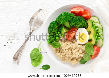 Healthy detox dish with egg, avocado, quinoa, spinach, fresh tomato, green peas and broccoli on white wooden background, top view #1029610756