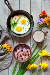 Healthy diet breakfast with spring morning mood, oatmeal porridge with nuts and blackberry, coffee and fried eggs in cast iron skillet on vintage wooden background. Top view