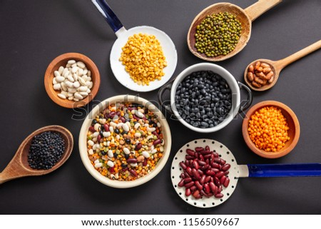 Healthy diet concept.Top view of fflat lay of assortment of legumes pulses on black tabletop background, in scoop, enameled bowl and ladles.