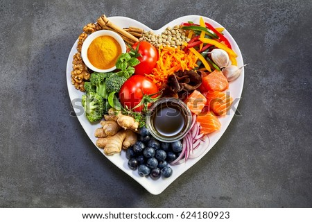 Healthy diet for the cardiovascular system with a heart-shaped plate of acai, lentils, soy sauce, ginger, salmon, carrot, tomato, turmeric, cinnamon, walnuts, garlic, peppers, broccoli, basil, onion #624180923