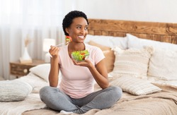 Healthy diet for weight loss concept. Happy black woman eating yummy vegetable salad on bed at home, blank space. Positive African American lady having balanced breakfast