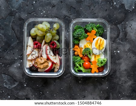 Healthy diet snack, breakfast lunch box on dark background, top view. Boiled egg, fresh vegetables and fruits - tasty healthy food concept