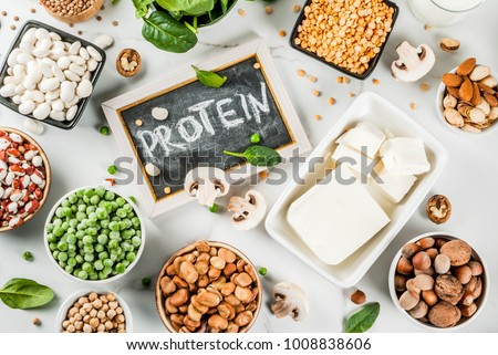 Healthy diet vegan food, veggie protein sources: Tofu, vegan milk, beans, lentils, nuts, soy milk, spinach and seeds. Top view on white table.