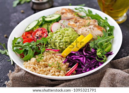 Healthy dinner. Buddha bowl lunch with grilled chicken and quinoa, tomato, guacamole, red cabbage, cucumber and arugula on gray background.