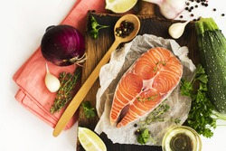 Healthy dinner ingredients: raw salmon steak ready for cooking and fresh vegetables over white table. Top view
