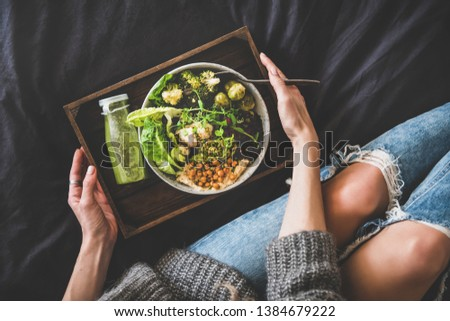 Healthy dinner, lunch in bed. Vegan superbowl or Buddha bowl with hummus, vegetable, fresh salad, beans, couscous and avocado, green smoothie on tray and woman in jeans eating with fork, top view
