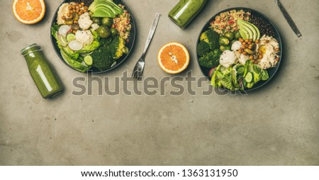 Healthy dinner, lunch setting. Flat-lay of vegan superbowls or Buddha bowls with hummus, vegetable, salad, beans, couscous, avocado and green smoothies in bootles, top view, copy space