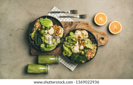 Healthy dinner, lunch setting. Flat-lay of vegan superbowls or Buddha bowls with hummus, vegetables, fresh salad, beans, couscous and avocado on wooden board and green smoothies, top view