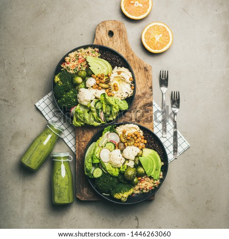 Healthy dinner, lunch setting. Flat-lay of vegan superbowls or Buddha bowls with hummus, vegetables, fresh salad, beans, couscous and avocado on board and green smoothies, top view, square crop