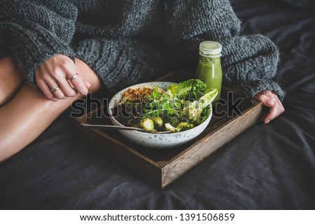 Healthy dinner, lunch setting. Vegan superbowl or Buddha bowl with hummus, vegetable, salad, beans, couscous and avocado, smoothie on tray and woman in warm sweater sitting near in bed