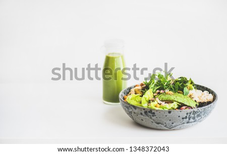 Healthy dinner or lunch at home. Vegan superbowl or Buddha bowl with hummus, vegetable, fresh salad, beans, couscous and avocado and green smoothie in bottle over white background, copy space