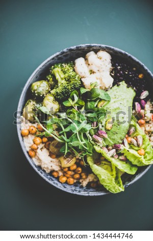 Healthy dinner or lunch at home. Vegan superbowl or Buddha bowl with hummus, vegetable, fresh salad, beans, couscous and avocado on dark background, top view