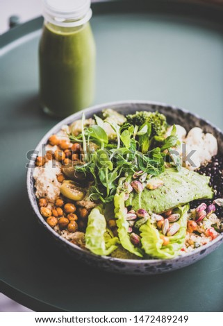 Healthy dinner or lunch at home. Vegan superbowl or Buddha bowl with hummus, vegetable, fresh salad, beans, couscous and avocado and green smoothie in bottle on table